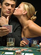 Woman kissing man´s cheek at poker game