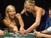 Upset woman taking poker chips at poker game