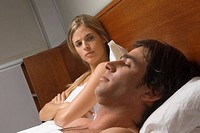 Upset woman in bed with man
