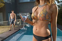 Woman in bikini near pool with man in background