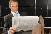 Businessman reading a financial newspaper in an office