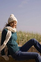Young happy woman in winter clothing on the beach