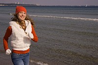 Happy woman in winter clothing running on the beach