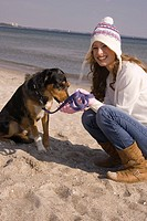 Young woman in winter clothing with dog at the beach