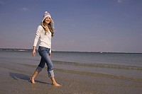 Happy woman in winter clothing walking on the beach