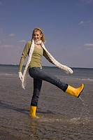 Young woman in winter clothing and boots splashing water at the beach