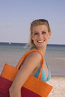 Young happy woman with beach bag at the beach