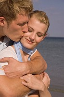 Young man kissing woman on the cheek at the beach