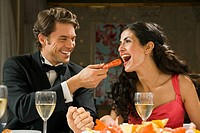 Young man feeding a prawn to a young woman and smiling