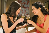 Two young women toasting with wine glasses in a restaurant