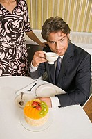 High angle view of a young man holding a cup of tea and sitting in front of a cake