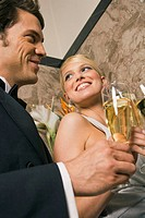 Close-up of a young couple toasting with champagne flutes
