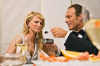 Mature man feeding caviar to a young woman