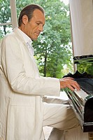 Side profile of a mature man playing a piano
