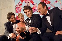 Three men and a woman celebrating with champagne
