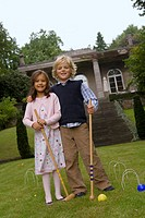 Portrait of a boy and a girl holding croquet mallets