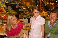 Portrait of a girl standing with her parents in a fruit market and smiling