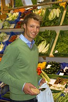 Portrait of a mid adult man standing in a supermarket and smiling