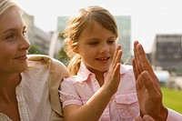 Close-up of a girl giving high-five to her father's hand and her mother looking at them