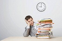 Businessman next to stack of paperwork (thumbnail)