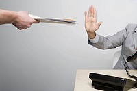 Businessman holding hand up to paperwork (thumbnail)