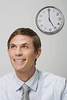 Businessman next to wall clock