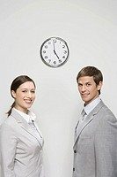 Business people standing next to clock