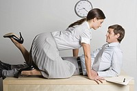 Businesswoman climbing on businessman on desk