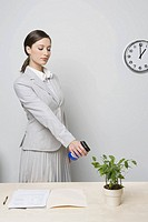 Businesswoman watering plant