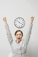 Businesswoman cheering under clock