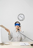 Businesswoman blindfolded at desk