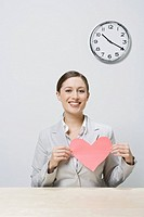 Businesswoman holding cut-out heart