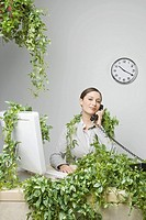 Businesswoman in plant covered office