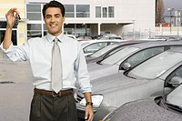 Man holding car keys at car dealership