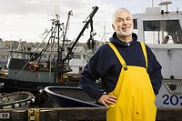 Senior male fisherman in front of fishing boat