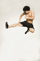 Bare-chested man jumping and kicking