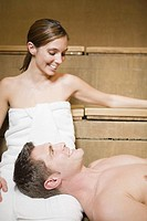 Man resting head on girlfriendÆs lap in sauna