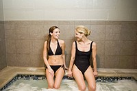 Two women sitting on edge of hot tub