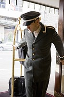 Bellhop pulling luggage cart (thumbnail)