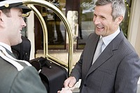 Businessman tipping bellhop (thumbnail)