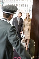Bellhop opening door for couple