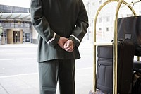 Bellhop with hands behind back