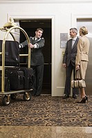Bellhop pulling luggage cart onto elevator