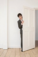 Businessman hiding behind a door (thumbnail)