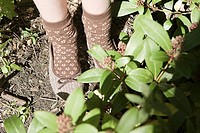 Child wearing brown slippers in garden