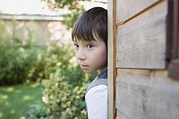Boy hiding behind a shed