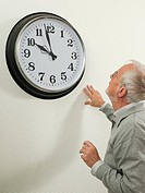 Senior man looking at a large clock
