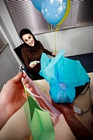Pregnant office worker receiving presents at party