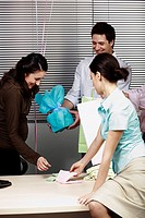 Pregnant office worker receiving presents at party (thumbnail)