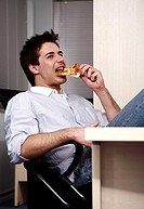Office worker eating a pizza slice at desk